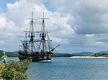A three-masted sailing ship with its sails furled, sitting motionless on a body of water. A beach and forested hills are in the background.