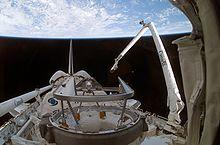"A shuttle in space, with Earth in the background. On the right, a mechanical arm labeled ""Canada"" rises from the shuttle"