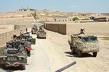 Convoy of Jeeps carrying camouflaged soldiers across desert.