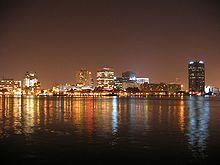 Several tall towers lit at night form a skyline over a calm stretch of water, in which the lights are reflected.