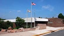 An entrance to a school below a white concrete overhang with red brick walls. National and local flags fly next to a circle of five rocks.