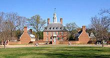 A three story red brick colonial style hall and its left and right wings during winter.
